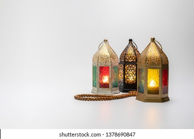 Ramadan Lanterns grouped together isolated on white surface with rosary beads in front.