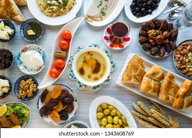 Ramadan,iftar,beginning meal before main menu with traditional soup,date fruits,olives,Ramadan bread,water walnut on the blue table with other foods.Special design.,top view.