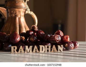 RAMADHAN text with dates fruit and arabic brass teapot on wooden table top.