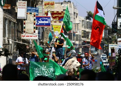 RAMALLAH, PALESTINE - AUGUST 17, 2014: A protester wearing a Guy Fawkes mask stands amidst a crowd at a Hamas rally in Ramallah, Palestine on August 17, 2014.
