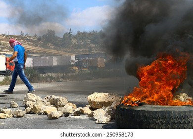 RAMALLAH, PALESTINE - AUGUST 9, 2014: A masked Palestinian strides past a burning tire during clashes with Israeli soldiers at Ofer Prison in Ramallah, Palestine on August 9, 2014.