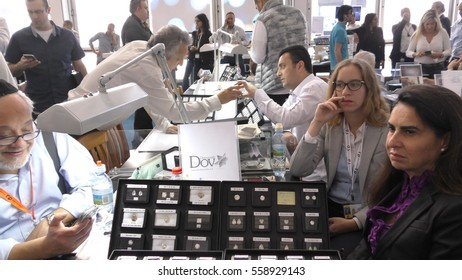 RAMAT GAN, ISRAEL, FEBRUARY 16, 2016: A trader displays perfectly shaped brilliant diamonds while negotiating on the smartphone in the Diamond Trading Hall Bursa during International Diamond Week