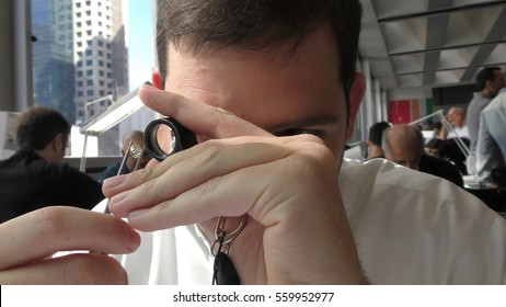 RAMAT GAN, ISRAEL, FEBRUARY 16, 2016: Jeweler examining diamond thoroughly through loupe in the Diamond Trading Hall Bursa during International Diamond Week, where buyers and sellers meet