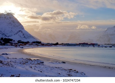 Ramberg beach in winter. The low winter sun is  shining through the sky, over the small fishing village of Ramberg.