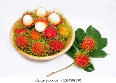 Rambutan fruit in wooden bowl. Isolated on white background.