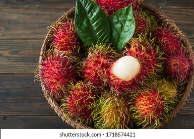 Rambutan, Thai fruits in a bamboo basket placed on an old wooden table