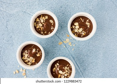 Ramekins filled with homemade chocolate pudding, decorated with roasted almond slivers, on light blue concrete background with copy space. Top view.