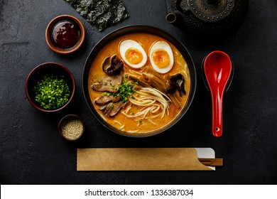 Ramen asian noodle in broth with Beef tongue meat, mushroom and Ajitama pickled egg in bowl on dark background