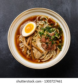Ramen asian noodle in broth with meat and Ajitama pickled egg in bowl on dark background