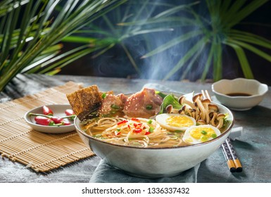 Ramen asian noodle in broth with meat and pickled egg in bowl on dark background.