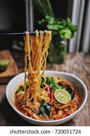 Ramen noodle with chanterelle mushroom in hot and spicy Thai style Tomyum soup. with lemon, chilis,coriander, lemon grass, kaffir or lime leaf and galangal. In ceramic bowl hand holding chopstick.