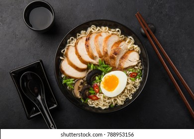 ramen noodle soup with chicken, shiitake mushroms and egg in black bowl, top view