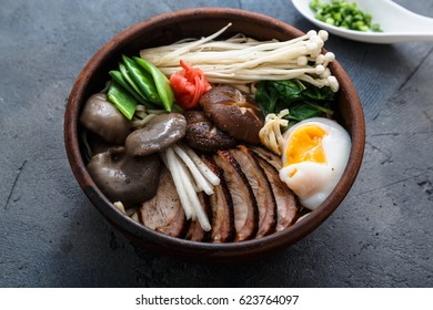 Ramen noodles bowl with egg, enoki, shiitake mushrooms, duck and onion