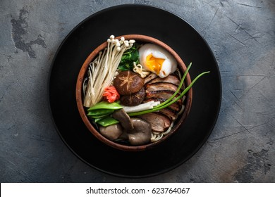 Ramen noodles with duck, egg, enoki and shiitake mushrooms with broth on dark background
