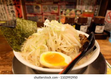 Ramen restaurant in Japan. There are sprouts, boiled egg and sasame in ramen bowl.