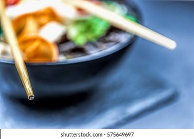 ramen soup in black bowl on black background - close up