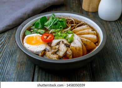 Ramen soup with chicken in the plate on blue wood table