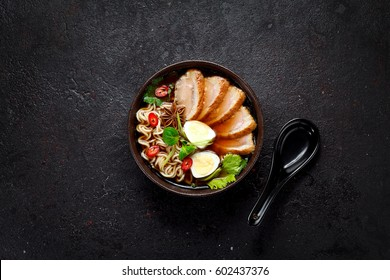 Ramen soup on a black bowl over dark stone background.