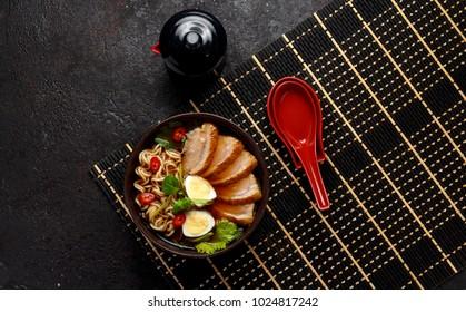 Ramen soup over dark background.