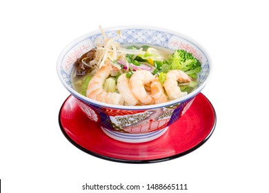 Ramen Soup with Shrimp in traditional Asian bowl and red plate isolated on white background.