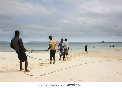 RAMENA, MADAGASCAR - APRIL 19, 2016: African fisherman pulling back huge fishing net on the shore of indian ocean in Ramena, Madagascar