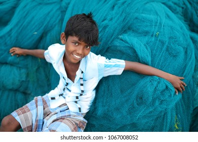 RAMESWARAM - INDIA - JANUARY 21, 2017: Unidentified young fisherman sits on a fishing net in a traditional fishing village on January 21, 2017 in Rameswaram, India.