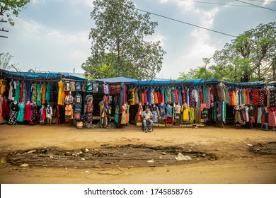 Ramgarh, Jharkhand, India - May 05 2019: A shopkeeper sitting in front of his road side garment & bag shop. Small business of India. Puddle of Mud in front of the shop. Highway side shop.