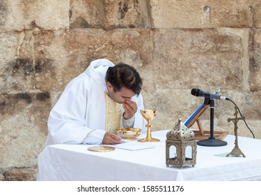 Ramla, Israel, December 07, 2019 : Priest takes communion during collective prayer on the ruins of the Byzantine church complex on the territory of Emmaus Nicopolis