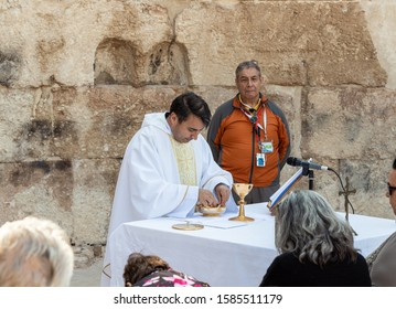 Ramla, Israel, December 07, 2019 : Priest makes communion at collective prayer on the ruins of a Byzantine church complex on the territory of Emmaus Nicopolis