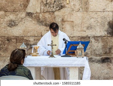 Ramla, Israel, December 07, 2019 : The priest makes a collective prayer on the ruins of the Byzantine church complex on the territory of Emmaus Nicopolis