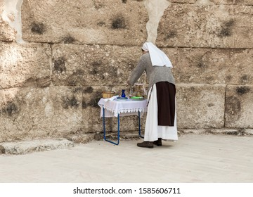 Ramla, Israel, December 07, 2019 : A nun is preparing a table with religious supplies for prayer on the ruins of a Byzantine church complex on the territory of Emmaus Nicopolis