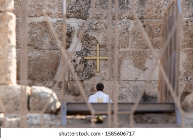 Ramla, Israel, December 07, 2019 : A view from afar of a priest doing religious prayer on the ruins of the Byzantine church complex on the territory of Emmaus Nicopolis