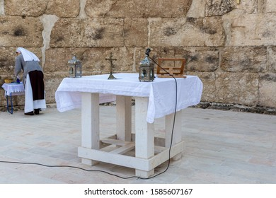 Ramla, Israel, December 07, 2019 : A cross with a crucifix, metal candlesticks, a microphone and a text with a prayer are on the table during a collective prayer in Emmaus Nicopolis