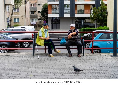 Ramnicu Valcea / Romania - August 25, 2020: Two elderly men social distancing on a outdoor bench while having a chat.