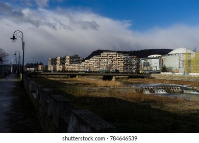 Ramnicu Valcea/Romania - December 23, 2017:View alongside the quay of Olanesti river, towards the town center of Ramnicu Valcea where modern architecture combine with socialist one.