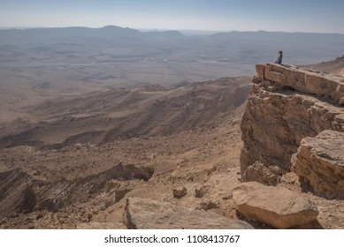 Ramon Crater (Makhtesh Ramon), Ramon Nature reserve, Mitzpe Ramon, Negev desert, Israel-December 21, 2015: A view of a tourist on the northern rim and of the world's largest desert crater below