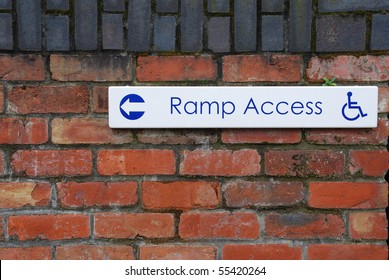 ramp access sign on a brick wall background