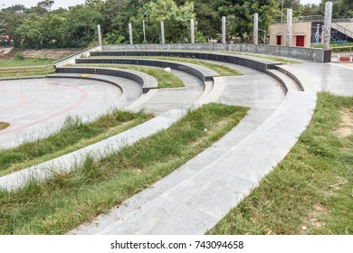 Ramp or cement steps or concrete steps with textured design and natural lawn formation. With group of trees in the background.