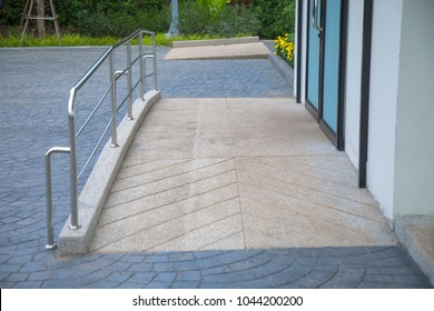 Ramp way with stainless steel handrail for support wheelchair disabled people infront of the disable toilet.