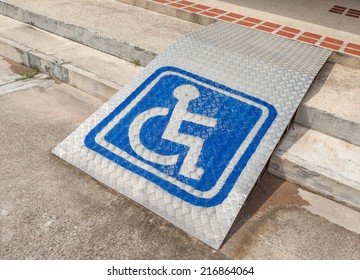 Ramped access, using wheelchair ramp with information sign on floor background for disabled people.