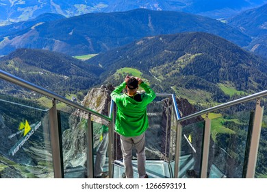 RAMSAU AM DACHSTEIN, AUSTRIA - Sep 13 2018: Happy Young man with backpack stands on observation deck of skywalk rope bridge Dachstein Mountains and enjoys the landscape in Austria