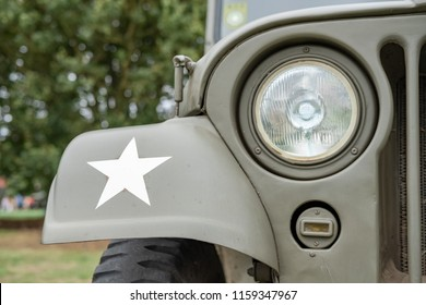 Ramsey, Cambridgeshire, UK - Circa August 2018:  close-up, shallow focus on a fully restored, iconic WW2 US Army Jeep showing a headlight, its painted white star and radiator. Seen at a military show.