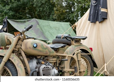 Ramsey, Cambridgeshire, UK - Circa August 2018: Detailed view of an iconic, WW2 German Army motorcycle seen at a german forward outpost during a film shoot. A uniform and tents can be seen in the set.