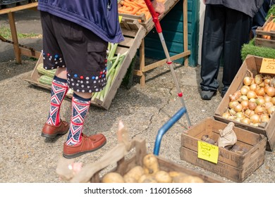 Ramsey, Cambridgeshire, UK - Circa August 2018: Waist down image of an endearing man seen wearing Union Jack socks while waiting to be served at a grocers. Various vegetables can be seen on display.