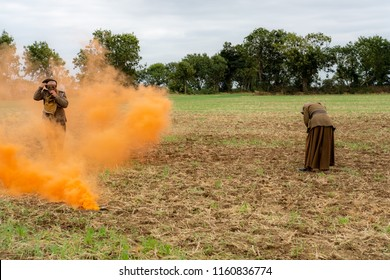 Ramsey, Cambridgeshire, UK - Circa August 2018: WW1 battle scene depicting a mustard gas attack on British troops, depicted by the orange smoke. A solder puts on a gas mask for protection in the smoke