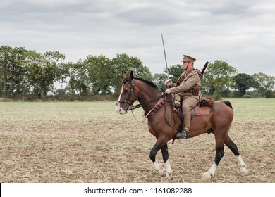 Ramsey, Cambridgeshire, UK - Circa August 2018: British Army WW1 cavalry soldier seen with his sword raised, ready to fight battle against an out of view enemy. He is seen on typical WW1 uniform.