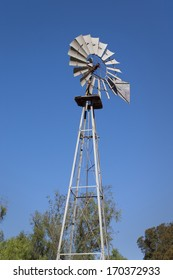ranch aluminum vintage windmill with blue sky in the background and trees on the bottom. Room for text