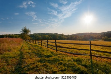 Ranch fence flows into a sun ready to set