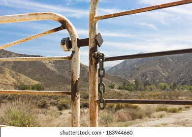 Ranch gate is locked and chained with mountains and brush in the background.