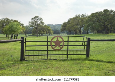 Ranch gate with a star in a Texas Hill Country pasture with trees